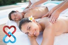 Złożony wizerunek cieszy się pary atrakcyjna para masuje poolside Fotografia Royalty Free