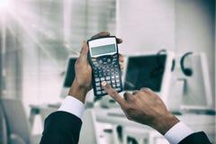 Złożony wizerunek cropped ręki biznesmen używa kalkulatora zdjęcia stock