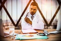 Złożony wizerunek doktorski przyglądający raport medyczny przy biurkiem Obraz Stock