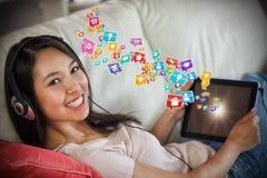 Złożony wizerunek dziewczyna używa jej pastylka komputer osobistego na kanapie i słuchanie muzyczny ono uśmiecha się przy kamerą  Zdjęcia Royalty Free