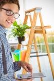Złożony wizerunek geeky biznesmen używa jego pastylka komputer osobistego zdjęcia stock