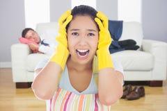 Złożony wizerunek jest ubranym fartucha i gumy rękawiczki zakłopotana kobieta Zdjęcia Stock