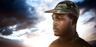 Złożony wizerunek jest ubranym nakrętkę rozważny żołnierz podczas gdy stojący zdjęcie stock