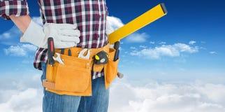 Złożony wizerunek jest ubranym narzędzie pasek repairman podczas gdy stojący z rękami na biodrach Obraz Royalty Free