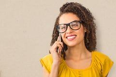 Złożony wizerunek jest ubranym szkła bizneswoman podczas gdy używać telefon komórkowego nad białym tłem Fotografia Stock