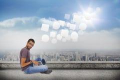 Złożony wizerunek jest ubranym szkła siedzi na podłogowym używa laptopie i patrzeje kamerę mężczyzna Zdjęcie Stock