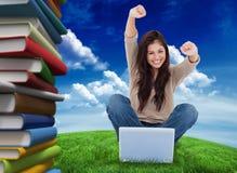 Złożony wizerunek kobieta patrzeje prosto naprzód gdy świętuje przed jej laptopem Obrazy Stock