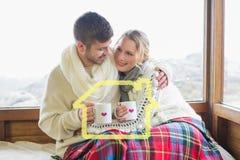 Złożony wizerunek kochająca para w zimy odzieży z filiżankami przeciw okno Zdjęcia Stock