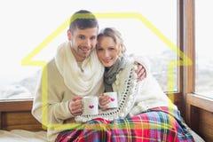 Złożony wizerunek kochająca para w zimy odzieży z filiżankami przeciw okno Zdjęcia Royalty Free