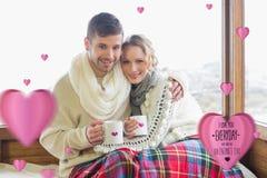 Złożony wizerunek kochająca para w zimy odzieży z filiżankami przeciw okno Fotografia Stock