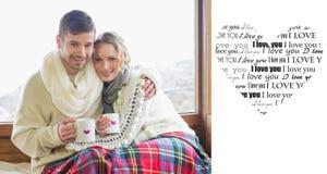 Złożony wizerunek kochająca para w zimy odzieży z filiżankami przeciw okno Obrazy Royalty Free