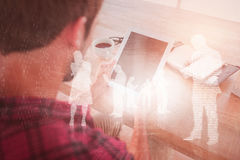Złożony wizerunek mężczyzna używa pastylkę na drewnianym stole fotografia stock