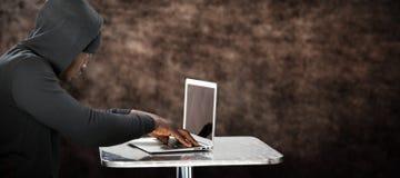 Złożony wizerunek męski hacker używa laptop na stole Obraz Royalty Free
