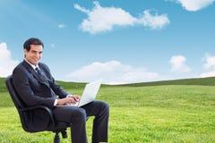 Złożony wizerunek młody biznesmena obsiadanie na karle pracuje z laptopem Fotografia Stock
