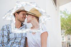 Złożony wizerunek młody modny pary obsiadanie na ławce wokoło całować Obrazy Stock