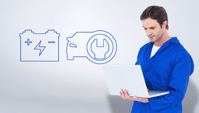 Złożony wizerunek mechanik używa laptop nad białym tłem Zdjęcia Royalty Free