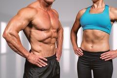 Złożony wizerunek midsection mięśniowy mężczyzna i kobieta z rękami na biodrze Zdjęcia Stock