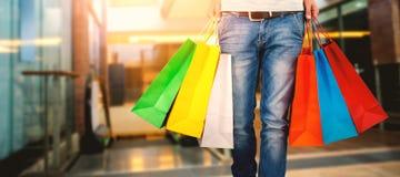Złożony wizerunek niska sekcja niesie kolorowego torba na zakupy mężczyzna Obrazy Stock