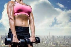 Złożony wizerunek niskiego kąta widok ćwiczy z dumbbells kobieta Fotografia Stock
