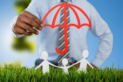 Złożony wizerunek ochraniający czerwonym parasolem rodzina zdjęcie royalty free