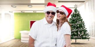 Złożony wizerunek ono uśmiecha się przy kamerą świąteczna para obraz stock