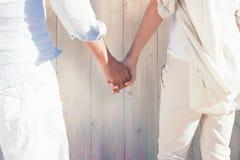 Złożony wizerunek para na plażowy przyglądającym out denne mienie ręki Obrazy Royalty Free