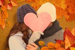 Złożony wizerunek para w ciepłym ubraniowym mienia sercu zdjęcia royalty free