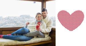 Złożony wizerunek para w zimy odzieży z filiżankami przeciw kabinowemu okno Obraz Royalty Free