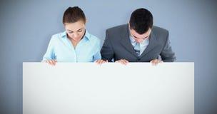 Złożony wizerunek partnery biznesowi patrzeje w dół przy znakiem trzymają obraz royalty free