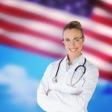 Złożony wizerunek piękna kobiety lekarka z rękami krzyżował w szpitalu obrazy royalty free