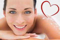Złożony wizerunek pokojowy brunetki lying on the beach z solankową pętaczką na tylny ono uśmiecha się przy kamerą Zdjęcia Royalty Free