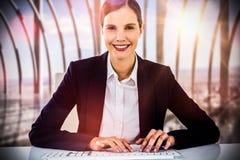 Złożony wizerunek portret pisać na maszynie na klawiaturze przy biurkiem uśmiechnięty bizneswoman zdjęcia stock