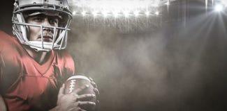 Złożony wizerunek poważny futbolu amerykańskiego gracz patrzeje oddalony podczas gdy trzymający piłkę Fotografia Royalty Free
