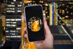 Złożony wizerunek ręki mienia telefon komórkowy przeciw białemu tłu Zdjęcie Stock
