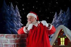 Złożony wizerunek Santa Claus mienia prezenta worek w komin Fotografia Stock