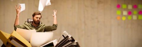 Złożony wizerunek sfrustowany biznesmena miotania papier podczas gdy siedzący przy stołem zdjęcia stock