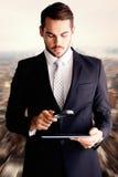 Złożony wizerunek skoncentrowany biznesmen używa powiększać - szkło fotografia stock