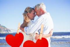 Złożony wizerunek szczęśliwa para na plażowym macaniu stawia czoło Obraz Stock