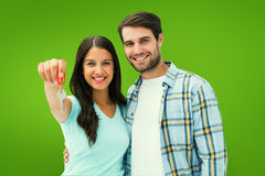 Złożony wizerunek szczęśliwa potomstwo para pokazuje nowego domu klucz Obraz Royalty Free