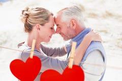 Złożony wizerunek szczęśliwa przytulenie para patrzeje each inny na plaży Zdjęcie Stock