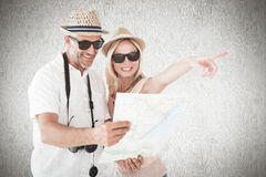 Złożony wizerunek szczęśliwa turystyczna para używa mapę i wskazywać obrazy royalty free