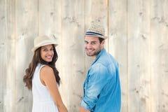 Złożony wizerunek szczęśliwe modniś pary mienia ręki i ono uśmiecha się przy kamerą Zdjęcie Royalty Free