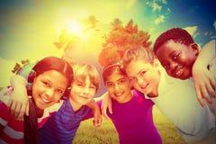 Złożony wizerunek szczęśliwi dzieci tworzy skupisko przy parkiem obrazy royalty free