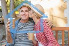 Złożony wizerunek szczęśliwy dorośleć pary pije kawę na ławce w mieście Obrazy Royalty Free