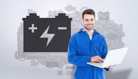Złożony wizerunek szczęśliwy młody męski mechanik używa laptop Obrazy Stock