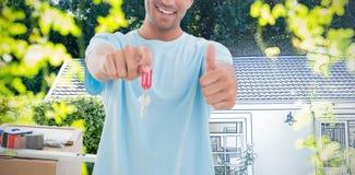 Złożony wizerunek trzyma out nowego domu klucz mężczyzna podczas gdy gestykulujący aprobatę zdjęcia royalty free