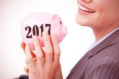 Złożony wizerunek trzyma piggybank rozochocony bizneswoman zdjęcie stock