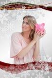 Złożony wizerunek trzyma prosiątko banka do jej głowy kobieta Fotografia Stock