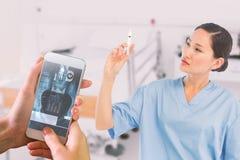 Złożony wizerunek trzyma zastrzyka w szpitalu poważna lekarka Obrazy Stock