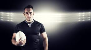 Złożony wizerunek twarda rugby gracza mienia piłka Zdjęcia Stock